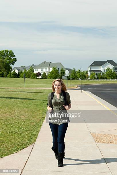 Female high school student walking along pavement
