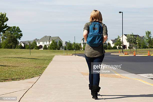 Female high school student walking along pavement