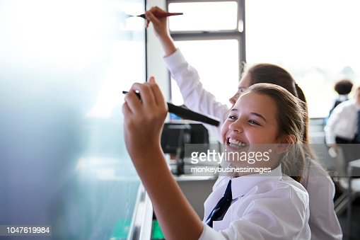 Female High School Students Wearing Uniform Using Interactive Whiteboard During Lesson : Stock Photo