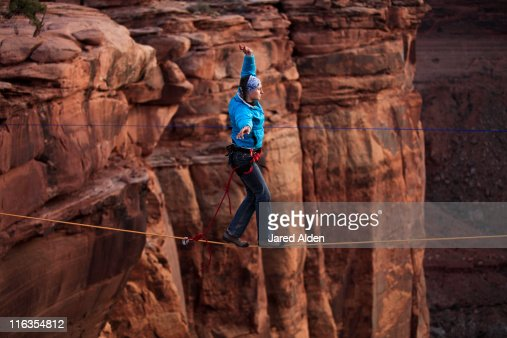 A female highliner walks across a highline at the Fruit Bowl in Moab, Utah, USA.
