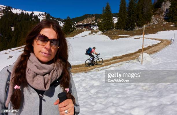 Female hiker and a mountain biker is walking a trail up to the mountain hut Priener Huette with a panoramic view on Wilder Kaiser in Austria on March...