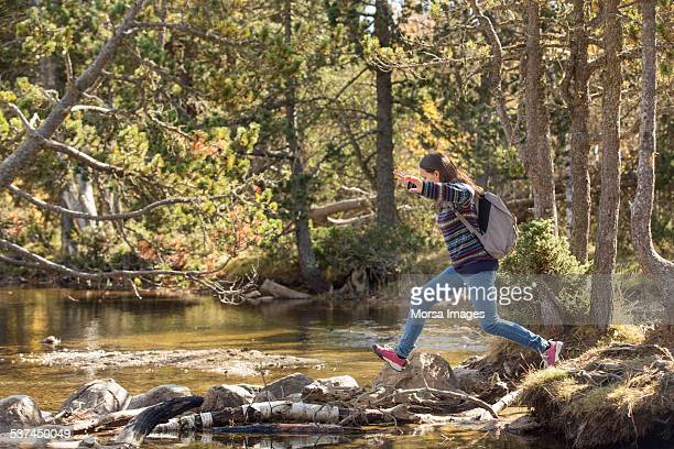 Female hiker crossing river in forest