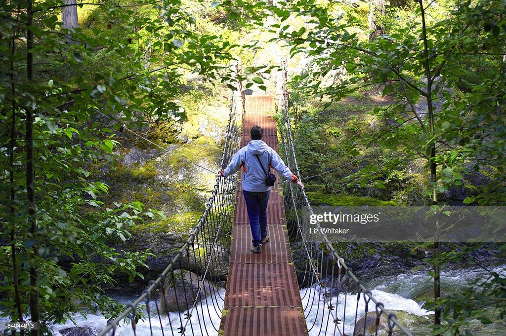 Female hiker crossing rope bridge, Canada