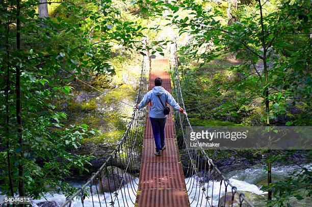 Female hiker crossing rope bridge, Canada