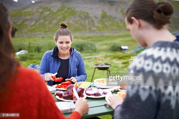 Female hiker having food with friends