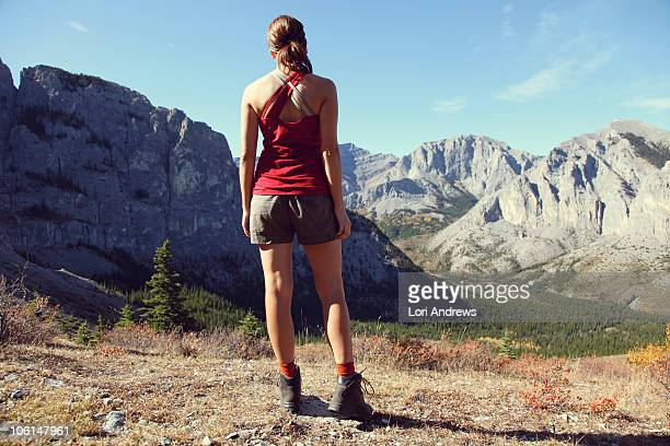 Female hiker in shorts over looking mountains