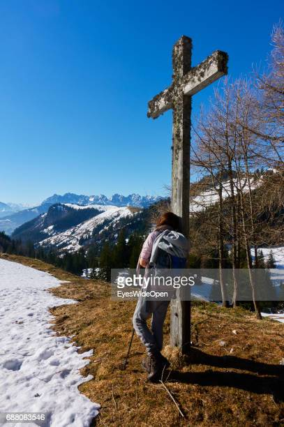 Female hiker is walking a trail up to the mountain hut Priener Huette with a panoramic view on Wilder Kaiser in Austria on March 26 2017 in Rosenheim...
