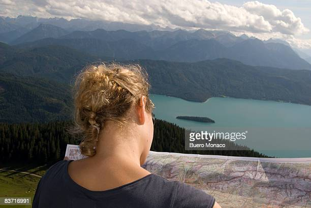 female hiker looking at a map, lake and mountains