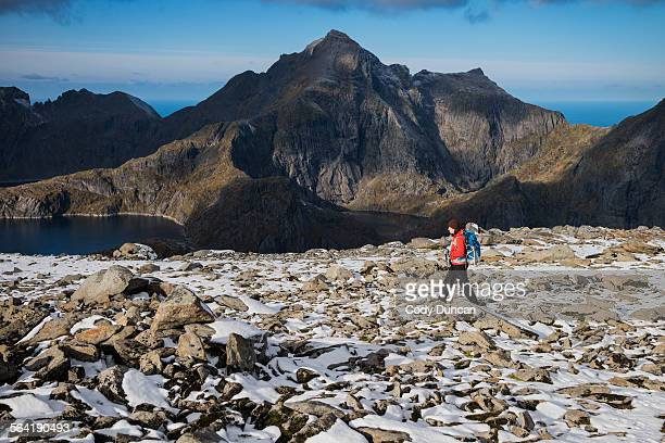 Female hiker on the rocky summit of Munken after a light autumn snow, Moskenesy, Lofoten Islands, Norway