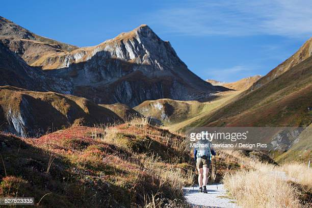 Female hiker on trail with grass covered slopes and mountain peak
