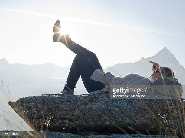 Female hiker pauses for rest on rock, mtns