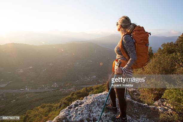 Female hiker pauses to look across hilly landscape