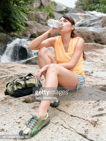 Female hiker resting on rock, drinking water : Stock Photo