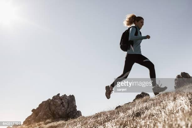 Female Hiker Running Across a Hill
