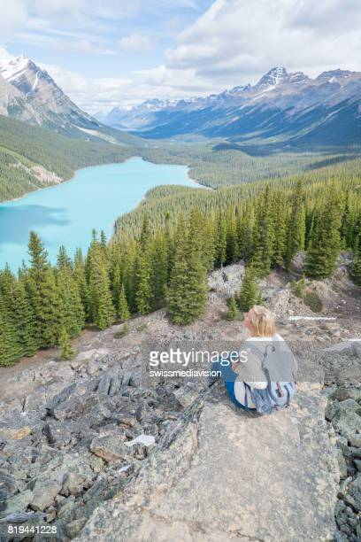 Female hiker sitting on last rock above blue lake