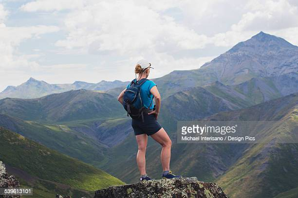 A female hiker stands looking over the landscape of mountains and valleys