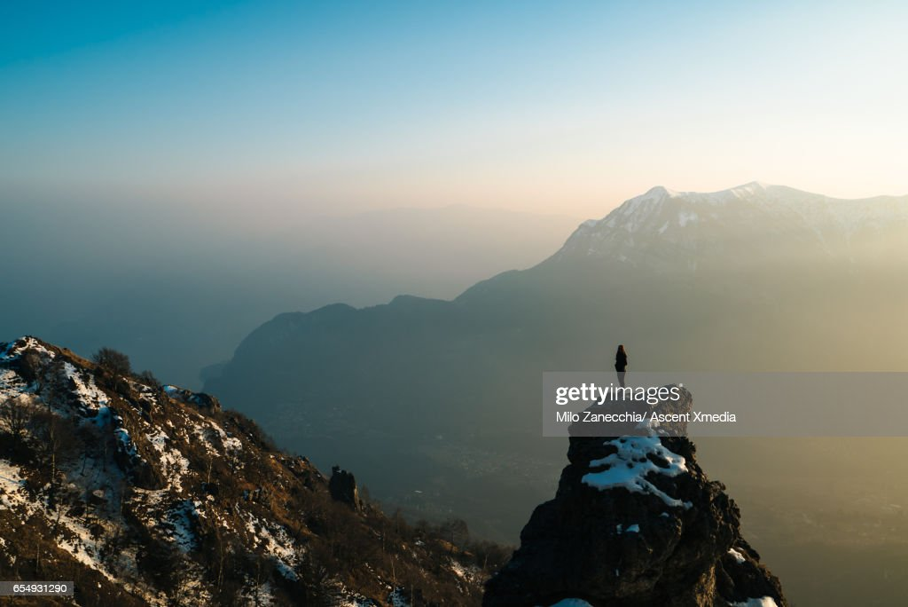 Female hiker stands on mountain summit, looks off : Stock Photo