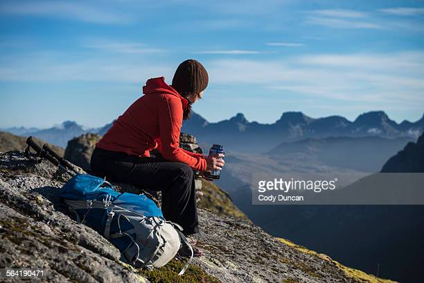 Female hiker takes a break and enjoys mountain views, Moskenesy, Lofoten Islands, Norway