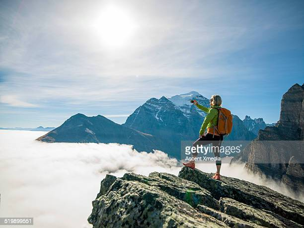 Female hiker takes picture of mountains and fog