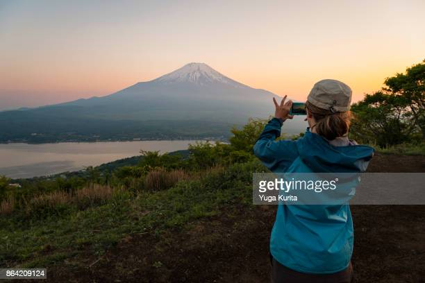 Female Hiker Taking a Photo of Mt. Fuji with her Smartphone
