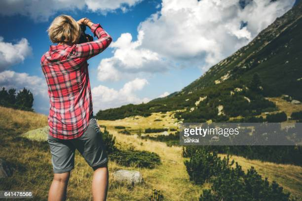 Female hiker taking photos in mountains