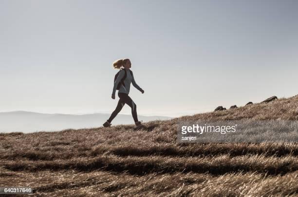 Female Hiker Walking Across a Hill