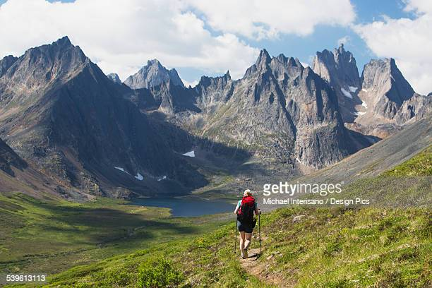 Female hiker walking on mountain trail with mountain lake, and valley with clouds and blue sky