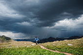 Female hiker walks along trail amid approaching rain in Ice Lakes Basin, San Juan mountains, Colorado, USA