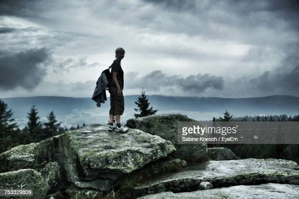 Female Hiker With Backpack Standing On Mountain Against Cloudy Sky