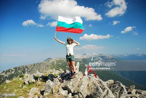 Female hiker with bulgarian flag on mountain peak