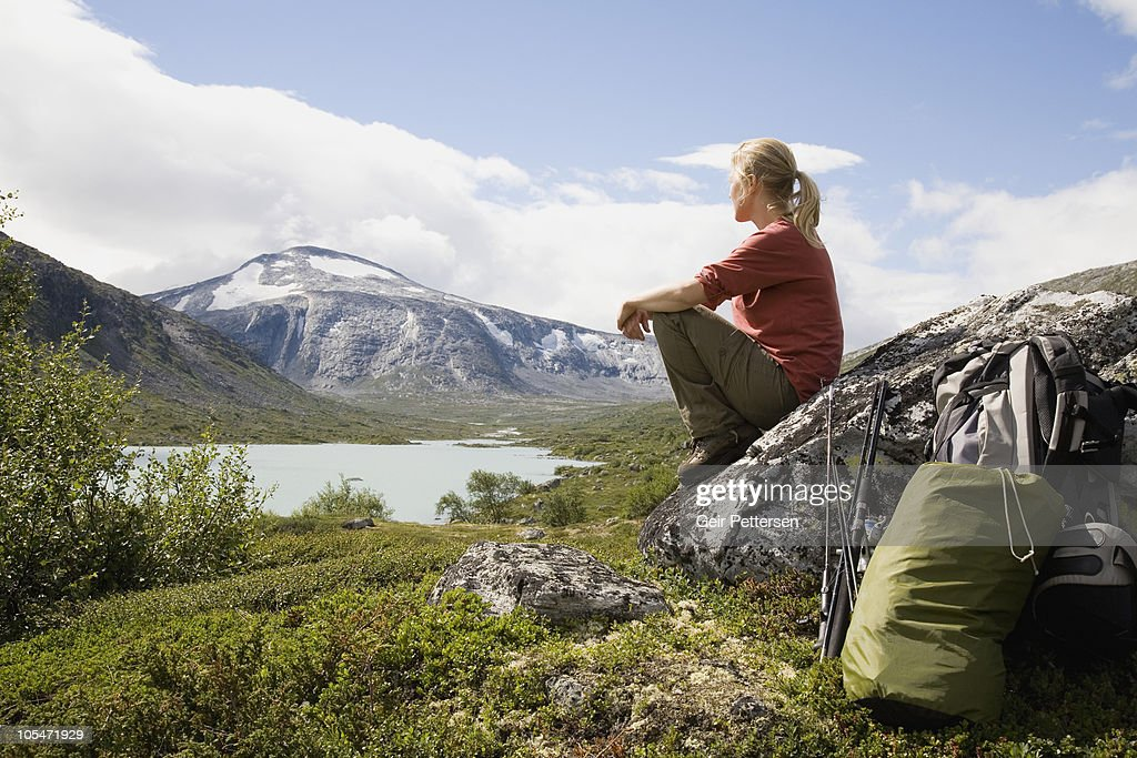 Female hiker with equipment overlooking scenery