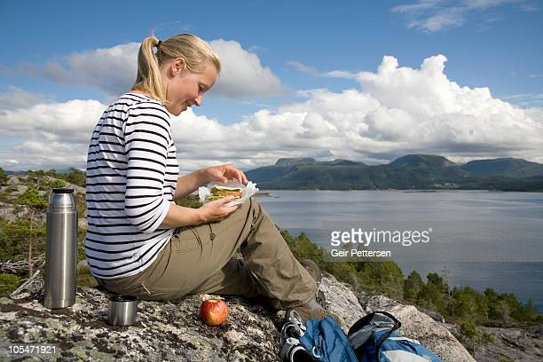 Female hiker with packed lunch on rock above fjord