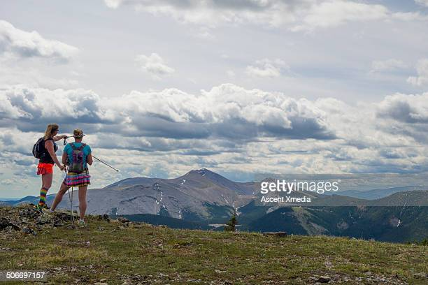 Female hikers pause on mountain summit, look off