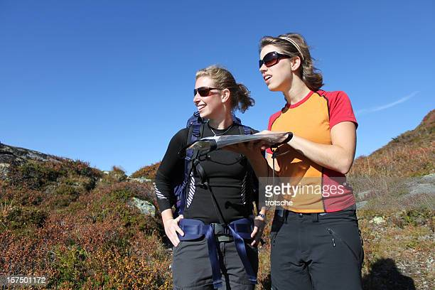 Female hikers reading map