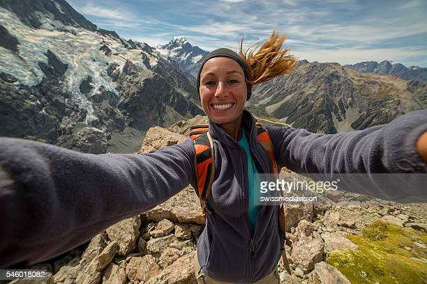 Female hiking reaches mountain top and takes selfie portrait
