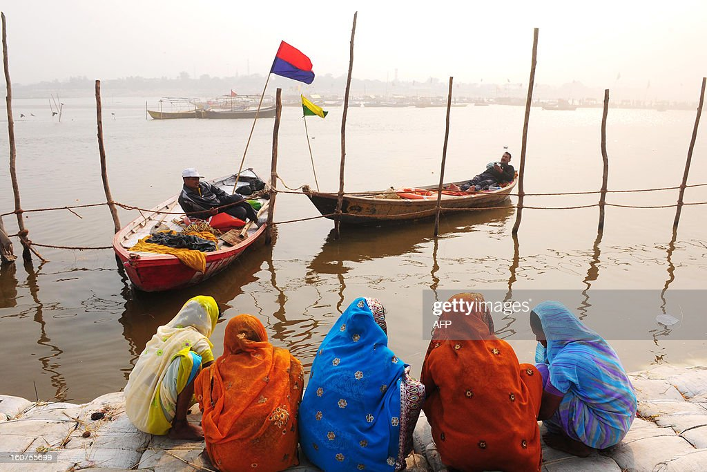 Female Hindu devotees perform a ritual at the confluence of the Rivers Ganges, Yamuna and mythical Saraswati during the Maha Kumbh festival in Allahabad on February 5, 2013. The Kumbh Mela in the town of Allahabad will see up to 100 million worshippers gather over 55 days to take a ritual bath in the holy waters, believed to cleanse sins and bestow blessings. AFP PHOTO/Sanjay KANOJIA