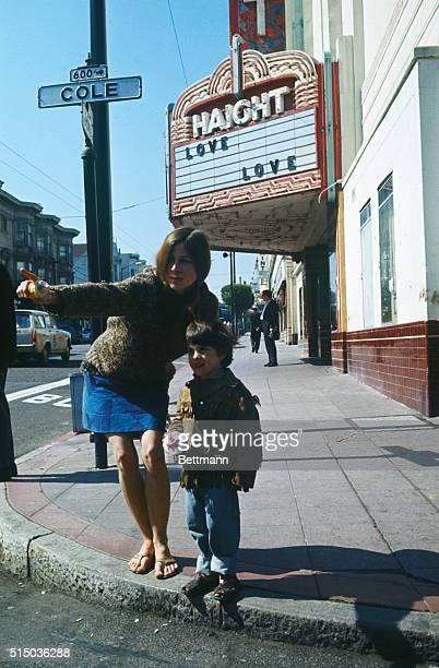 A female hippie and young boy stand on a street corner in the Haight Ashbury area Theater marquee in background displays the message 'Love'