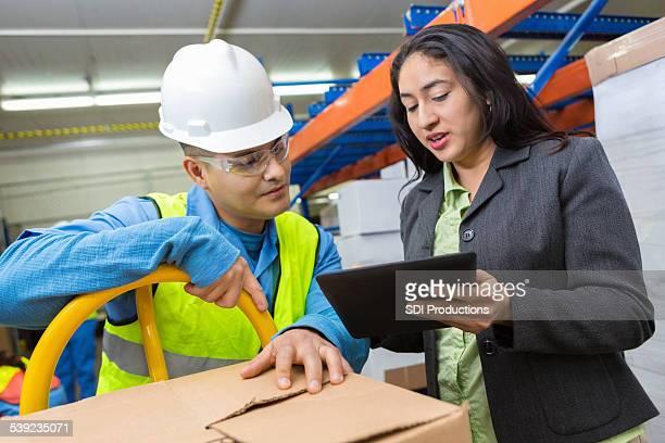 Gerente de almacén mujer hispana usando tableta digital con trabajador