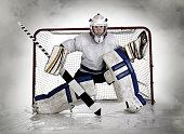 Studio pic of a teenage, female hockey goalie with a fog background.