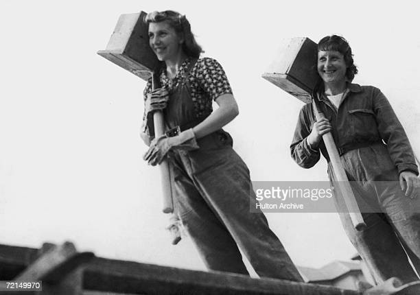 Female hod carriers at work on a construction site during World War II building homes for arms workers circa 1942