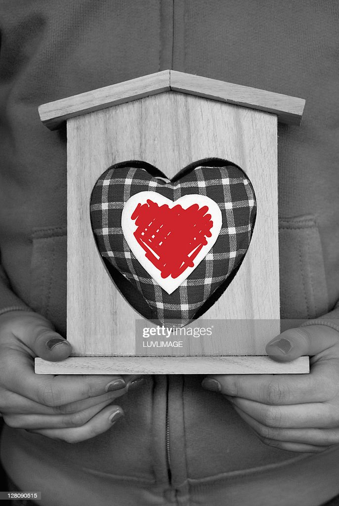 Female holding a wooden structure housing a heart-shaped cushion : Stock Photo