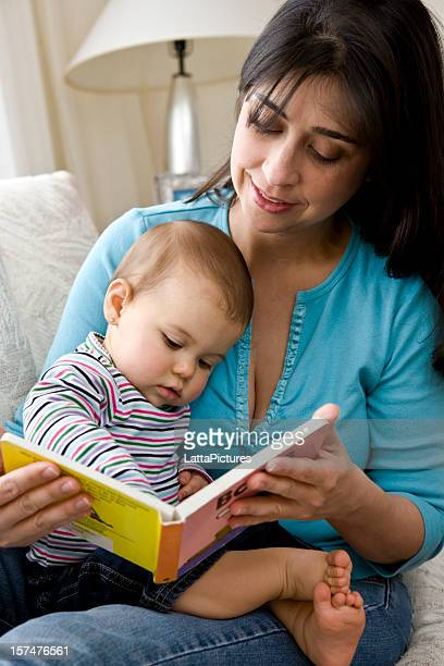 Female holding baby on lap and looking at book