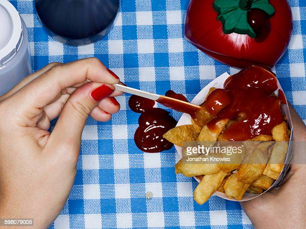 Female holding chips with ketchup, messy