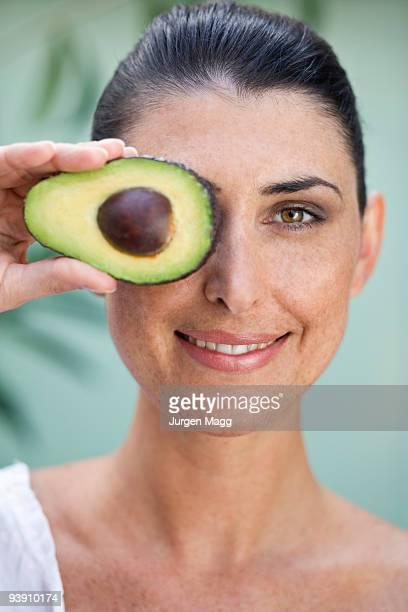 A female holding half an Avocado