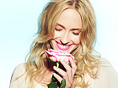Female holding pink rose to nose with eyes closed.