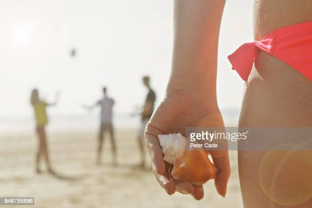 Female holding shell, friends playing in on beach