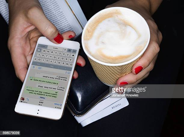 Female holding take away coffee, texting, close up