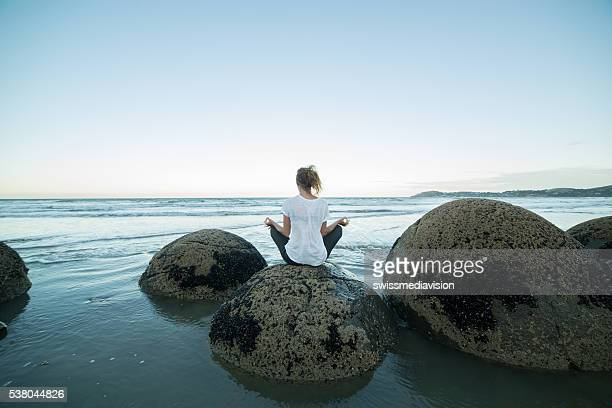 Female holding the lotus position yoga on boulder