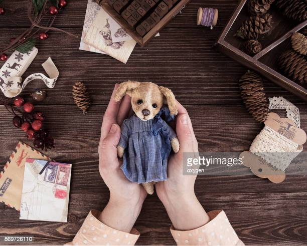 Female holding toy dog with on dark wooden table