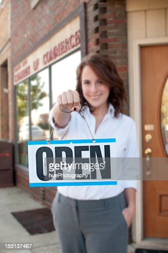 A female holding up a open for business sign